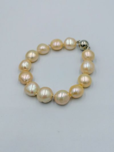 Peach-coloured button freshwater pearl bracelet .
