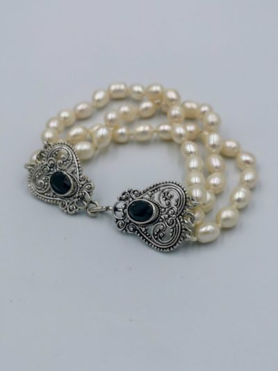 Three-row white freshwater pearl bracelet with fancy clasp.