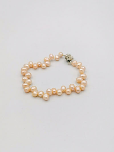 Bracelet comprising light apricot drop-shaped freshwater pearls, with a fancy clasp. Total bracelet length 19cm.