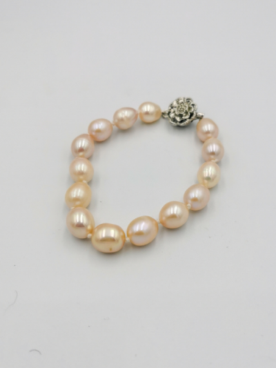 Bracelet comprising light apricot oval drop-shaped freshwater pearls, with a fancy clasp. Total bracelet length 18cm.